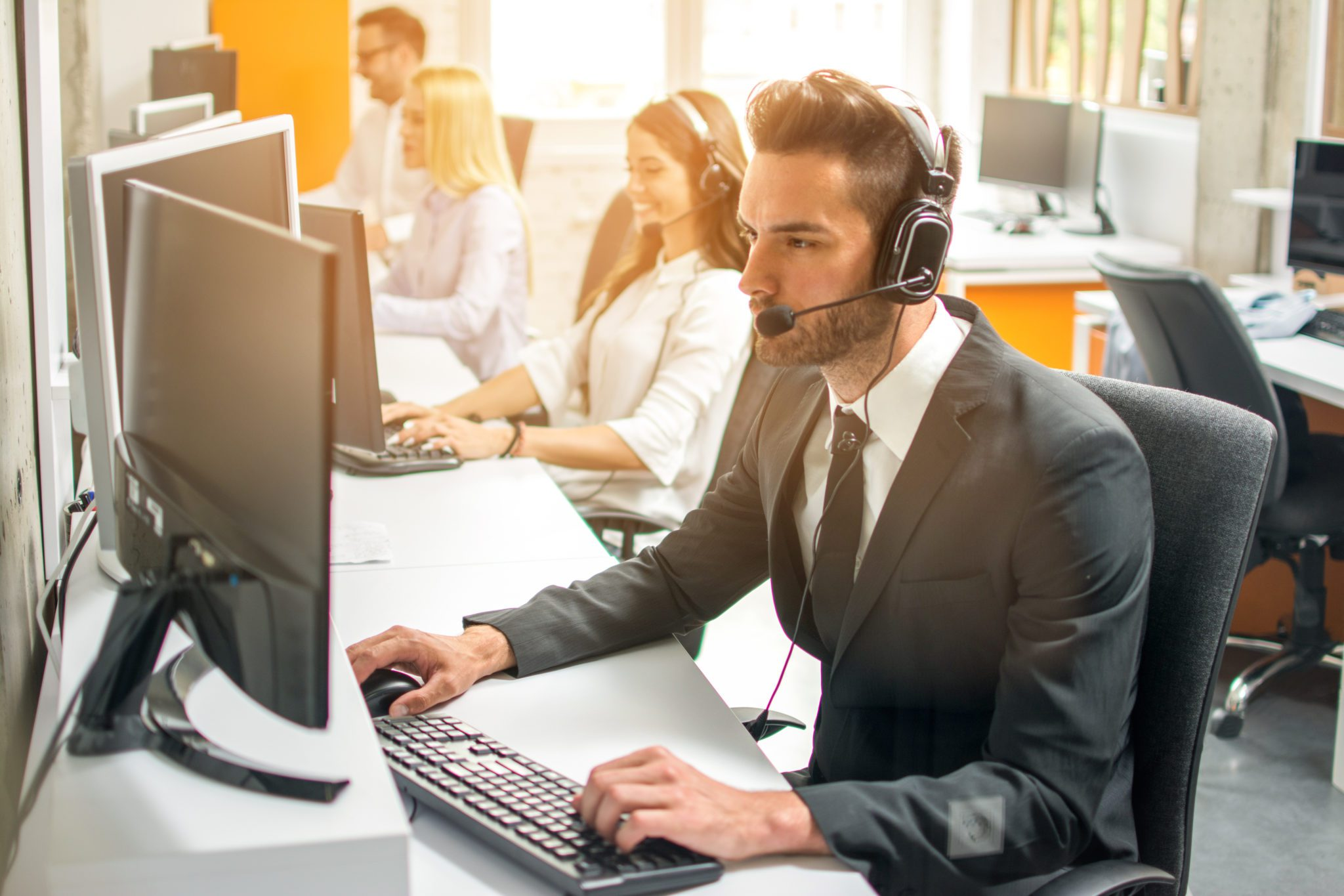 Friendly handsome man in suit with headset working with colleagues in call center