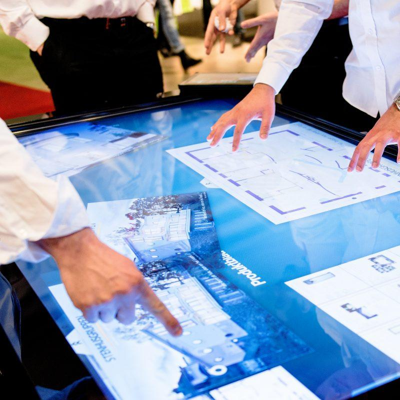 Multiple people in property development sector using multitouch on a large touchscreen panel
