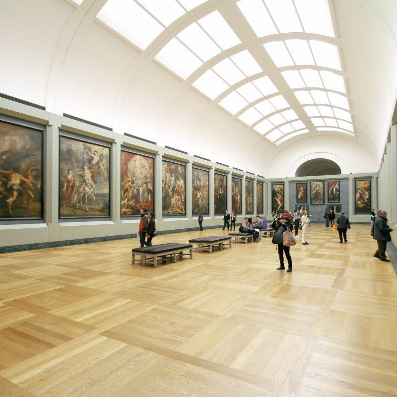 Image of the interior of an art gallery with visitors taking pictures and analysing the artwork